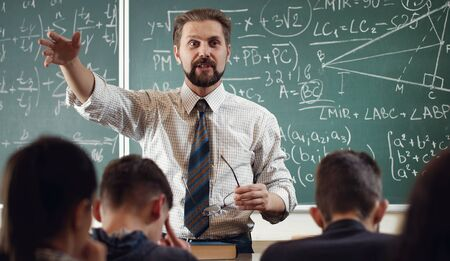 Enthusiastic mathematician explaining subject to students gesticulating with hand in schoolroom Banco de Imagens - 141679164