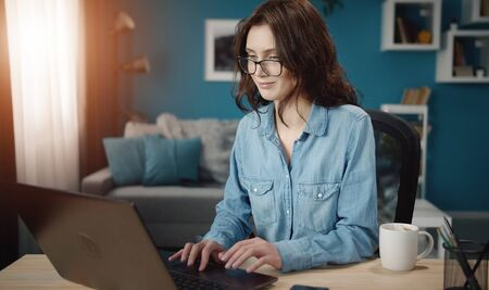 Contented young woman in glasses working on laptop sitting at table on living room background