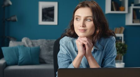 Portrait of musing young woman with her head rested on fists sitting in front of computer at home Stock Photo