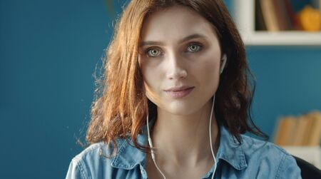 Headshot of serious young woman in denim shirt with earphones staying indoors looking at camera Stock Photo