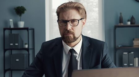 Portrait of serious businessman in classic wear and eyeglasses sitting at workplace looking camera