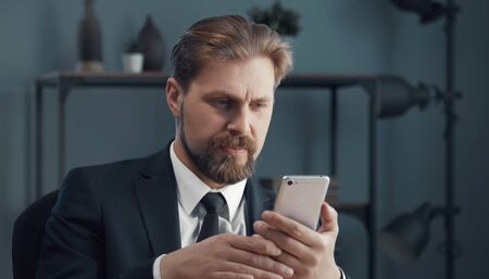Portrait of mature businessman in formal attire looking at smartphone screen sitting in office