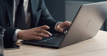 Close-up of businessman hands typing on laptop keyboard