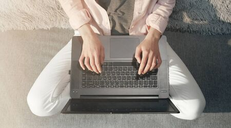 Top view of ladys lower body sitting in lotus position, hands typing on laptop keyboard, cropped