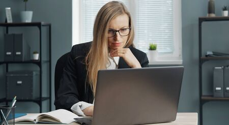 Focused mature business lady in formal suit and specs working on laptop sitting at office table