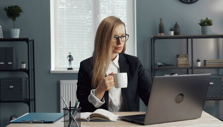 Busy adult businesswoman holding cup of coffee or tea while working on laptop sitting in office