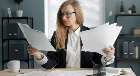 Concentrated blond business woman sitting at office desk holding heaps of documents, paper reports
