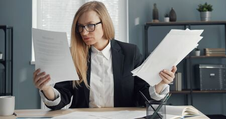 Focused blond business lady sitting at office table holding lots of docs reading paper reports