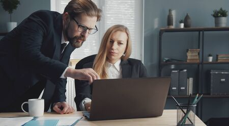Two business people working together discussing important issues using laptop computer in office Stock Photo