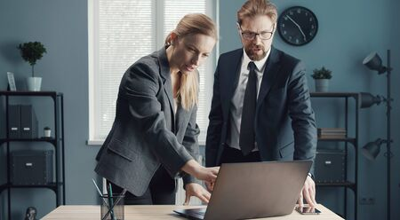Two colleagues looking at laptop screen discussing working issues standing at desk in office
