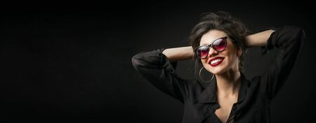 Playful glamorous young woman with arms behind head on black isolated background, copyspace