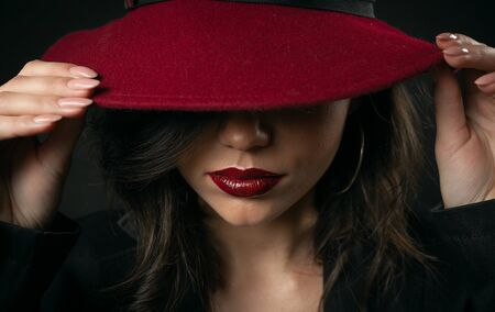 Close-up of sensual glamorous beauty hiding face under hat touching maroon wide brim with both hands
