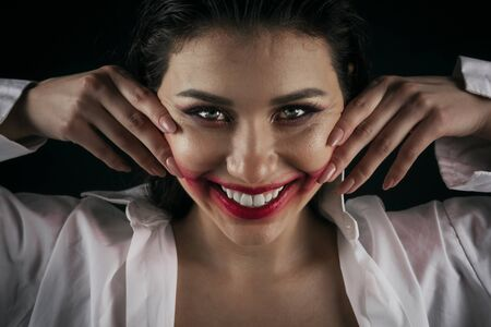 Portrait of crazy-looking woman smearing red lipstick on her face with both hands, black background Stock Photo