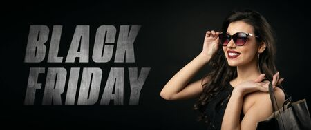 Smiling beauty touching sunglasses holding shopping bags on shoulder on Black Friday text background