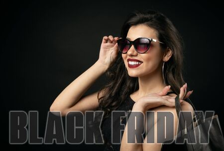 Portrait of cheery beauty touching sunglasses holding shopping bags, Black Friday text over picture Stock Photo
