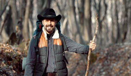 Happy male rambler with cowboy hat, hiking outfit, and stick walking in nature, shallow focus