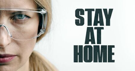 Half face of serious blond woman in goggles glasses, medical doctor, stay at home quarantine sign Stock Photo