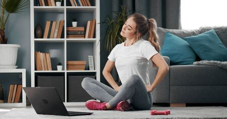 Young lady sitting with folded legs and inclined head on floor warming up before training