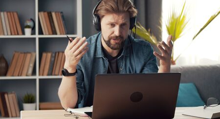 Adult man working remotely sitting at laptop with headset on staying in flat during quarantine Stock Photo