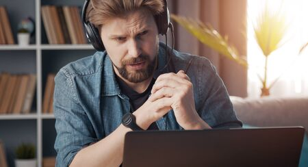 Front view of dutiful man with headset doing distance work looking at computer screen, lockdown
