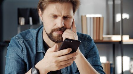 Cropped shot of pensive man holding smartphone looking at screen staying indoors, workplace at home