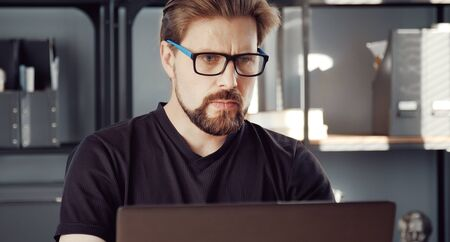 Focused mature man using computer working from home office during lockdown due to virus epidemic Stock Photo