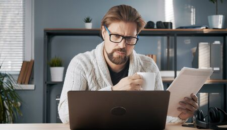 Busy adult male looking at laptop screen holding papers and cup working from home office