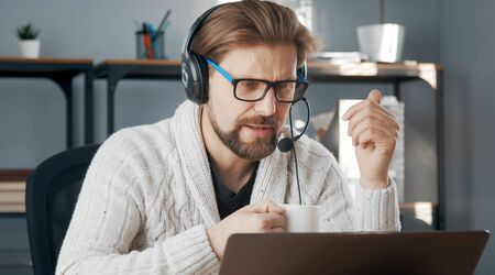 Casual-dressed male with headset teleworking sitting in front of computer, isolation due to epidemic