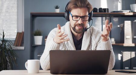Adult male working remotely sitting at laptop with headset on staying in flat during quarantine