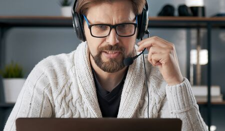 Headshot of dutiful male with headset doing distance work looking at computer screen, lockdown