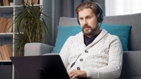 Male with headset teleworking sitting on floor leaning against sofa using laptop, lockdown