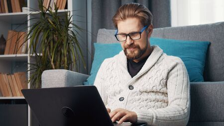Middle-aged male working from home sitting on floor leaning against couch using laptop, quarantine