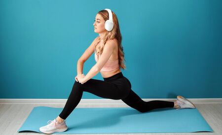 Young female in athletic clothes and headphones stretching legs muscles over isolated background Stock Photo