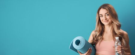 Portrait of young glad woman in sports bra holding exercise mat and water, sport and health concept