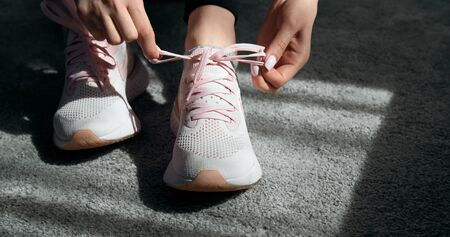 Close up of female hands tying sport shoes laces before training, indoors, sunlight on floor