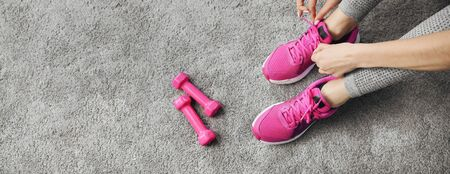 Close-up of female hands tying training footwear laces before indoor workout, dumbbells nearby