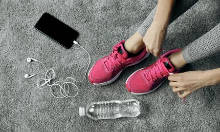 Top view of woman hands lacing pink running shoes close to phone and water bottle on gray flooring
