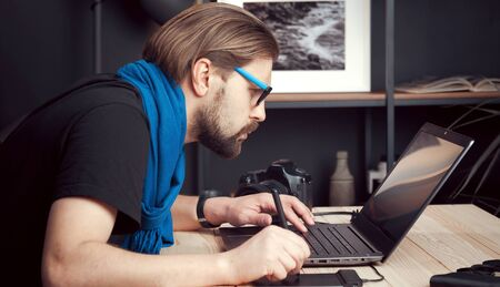 Portrait of male photographer processing retouching images using laptop and graphic drawing tablet