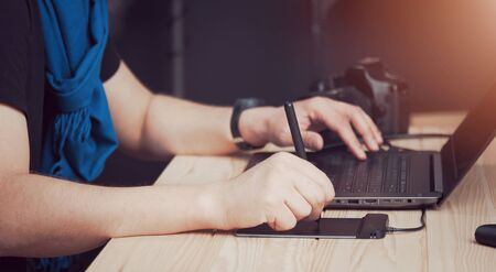Close-up of male photographer hands using laptop keyboard and drawing tablet, side view Stock Photo