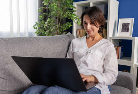 Relaxed woman in white shirt and blue jeans lying on cozy sofa and using wireless laptop. Mature female with short haircut spending free time at home with modern device.
