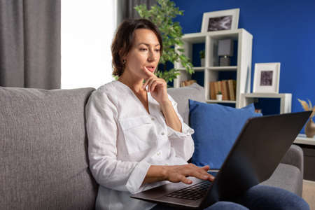 Mature woman in casual clothing sitting on grey couch and looking at computer screen with thoughtful facial expression. Concept of modern technology and human emotions.