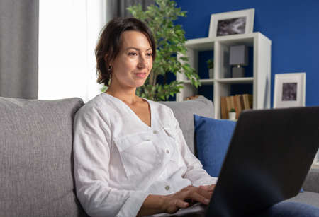 Smiling mature woman in white shirt relaxing on grey couch with wireless laptop. Beautiful female with dark hair using portable computer during leisure time at home. Stock Photo