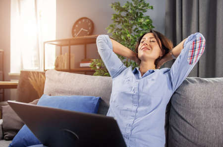 Charming woman in blue shirt sitting on couch with opened laptop and holding hands behind back. Tired lady with dark hair relaxing at home during remote work.