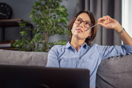 Thoughtful woman in eyeglasses and casual holding laptop on knees, looking aside while sitting on cozy sofa. Mature female with brown hair thinking about new working project. Stock Photo