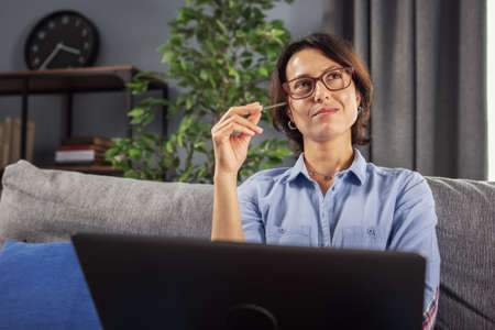 Happy mature woman in eyewear sitting on sofa with opened laptop and seeking for inspiration. Thoughtful lady in blue shirt needs to be productive at remote work from home.