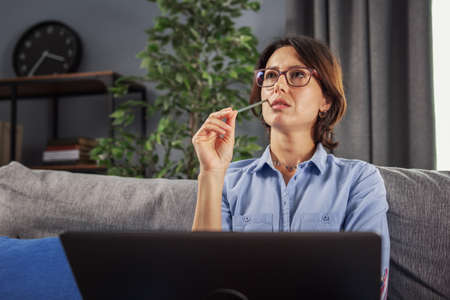 Thoughtful mature lady in eyeglasses holding pen near her cheek while sitting on couch and looking aside. Business woman with dark hair working on laptop at home.