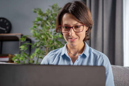 Portrait of confident mature woman in eyeglasses and blue shirt working on wireless laptop while sitting on grey sofa at home. Concept of people and modern technology.