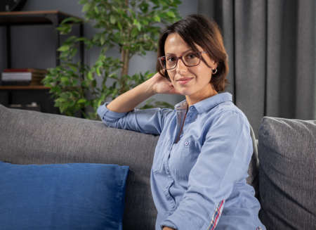 Portrait of attractive woman with dark hair relaxing on grey couch at home and looking at camera. Mature lady wearing eyeglasses and blue shirt during leisure time. Stock Photo