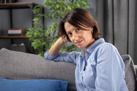 Mature brunette in casual clothing leaning on grey pillow on couch and looking at camera with penetrated glance. Concept of natural beauty and home relaxation.