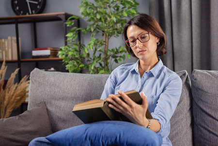Concentrated lady with brown hair relaxing on cozy sofa with interesting book. Beautiful woman in eyeglasses and casual clothing reading new literature at home. Stock Photo